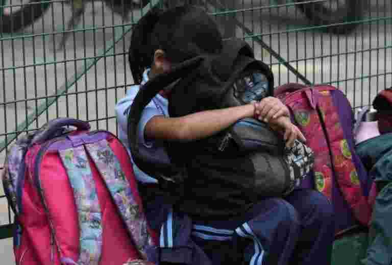 印度在学校投掷书,让年轻的学生携带沉重的袋子